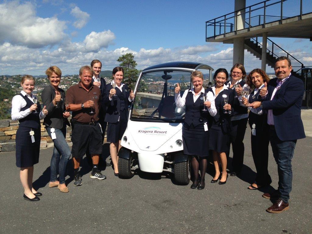 Kragerø Resort feiret Åse Haslum med Champagne. Åse står til høyre for golfbilen